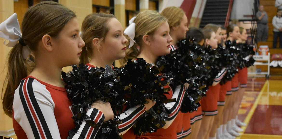 Cheerleaders holding their pom-poms to their hearts during the Pledge of Allegiance.