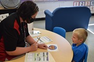 Instructor Whitney Burks works with an incoming preschooler during screening
