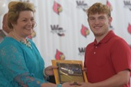 student receives plaque from Carol Ford