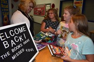 Monticello Orientation7th grader L'ton Crabtree, 4th grader Brianna Smith, and 4th grader Lavaya Crabtree looked at library books with Media Specialist Tracy Slagle
