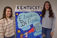 Girls holding banner they worked on at school