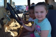 Preschoolers pretend to drive sheriff's jeep