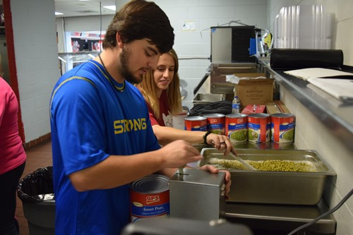 Volunteers help prepare meal