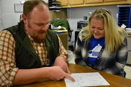 (L-R) Substitute Teacher Justin Cole talking to mother Brandi Rednour about her child Chandler Rednours work