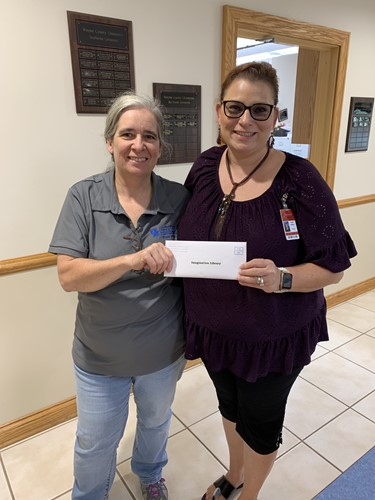 Extension bookkeeper Diana Cushman presented a $1,676 donation to Walker Early Learning Center principal Angela Ballinger