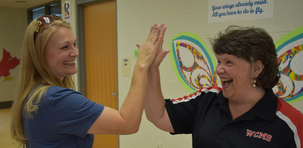 Parent Shannon Keene and 21st Century Coordinator Katherine Kidd high fived at middle school orientation
