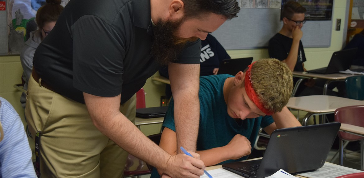 AP Literature and Composition teacher Jeremy Barnett assisting a student with an assignment.