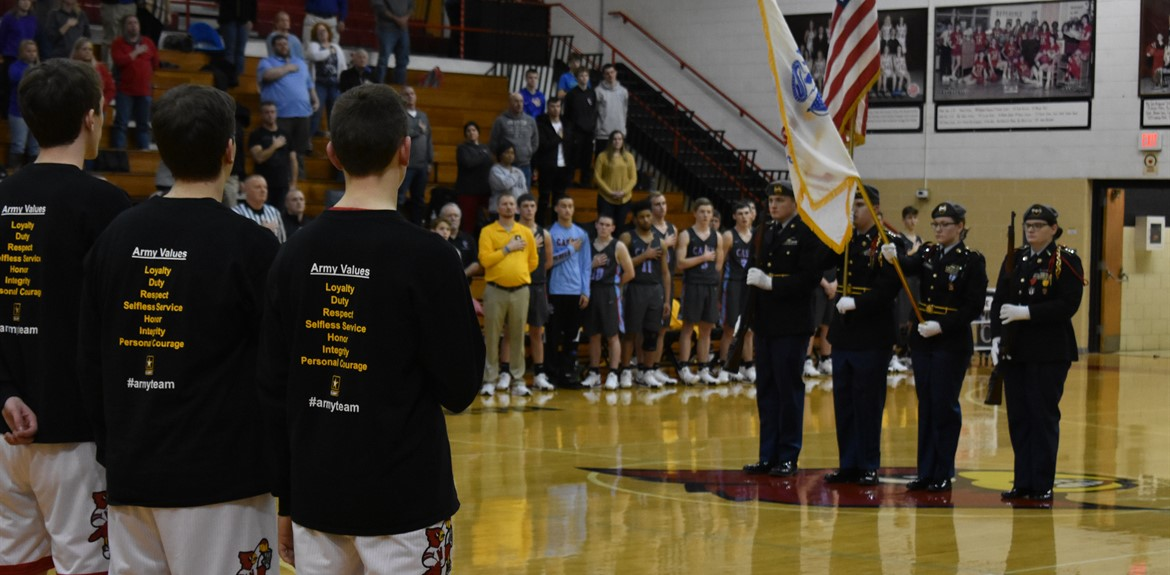 Cards stand at attention for the flag presented by the JROTC Color Guard