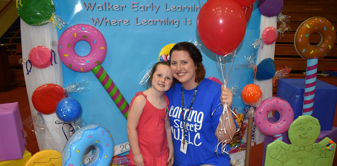 "Preschool Teacher Whitney Burks and daughter Daisey enjoying the Child Plus Fair Candyland booth for WELC ""Where Learning is Sweet"""