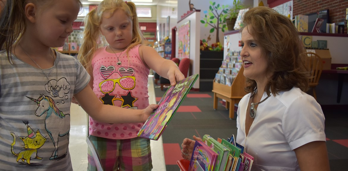Bell Elementary Media Specialist Nell Boils armed with books for students