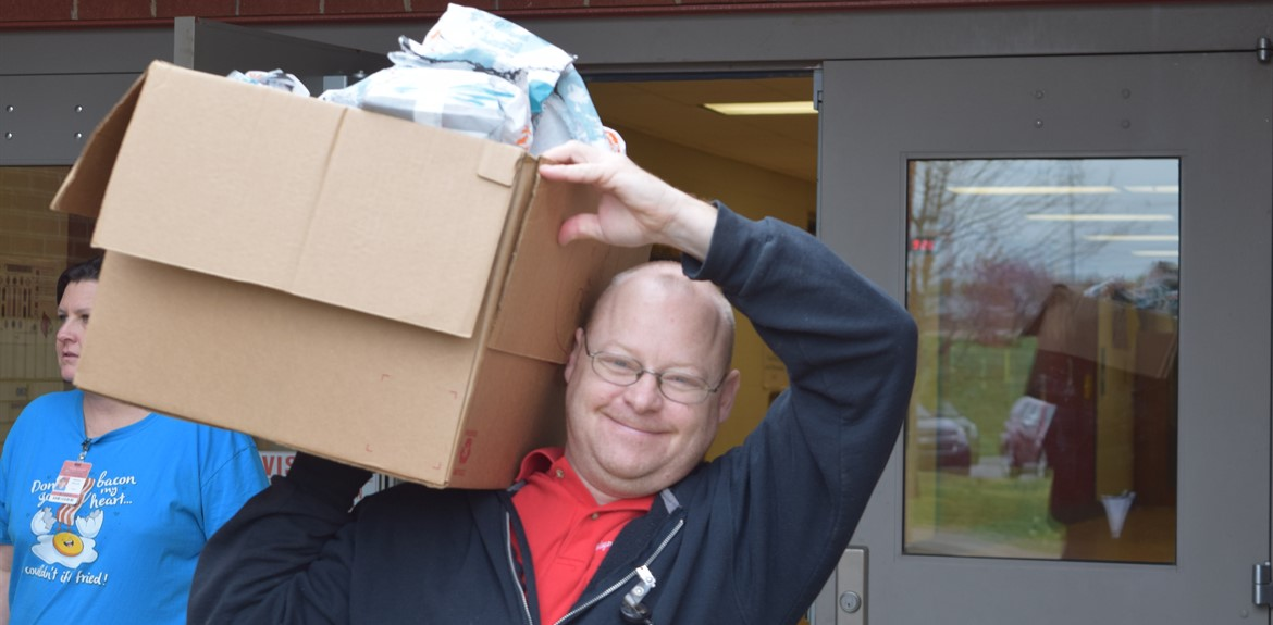 Ralph Reynolds carries out a load of food to a school bus distributing meals