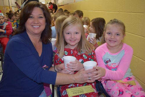 Teacher hands hot chocolate to two students