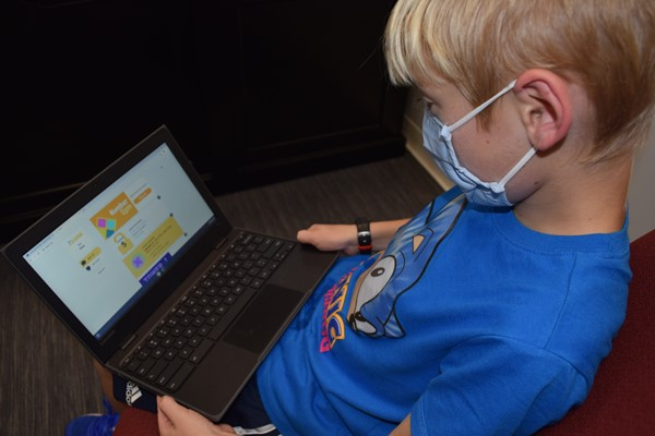 Fourth grader Silas Neal works on an assignment in Google Classroom away from his classroom.