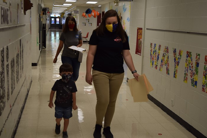 Para-educator Savannah Sumpter escorted 4-year-old Malachi Foster and his Mom Rebecca Foster to a classroom