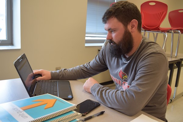 Sixth grade Math Substitute Teacher Kyle Gehring works on student assignments