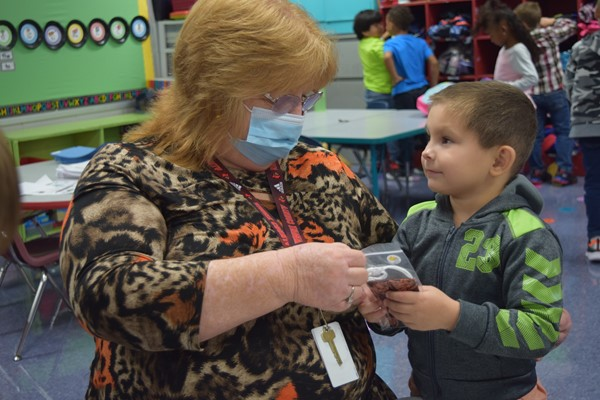 Kindergarten Instructional Aide checks out a mask a student selected