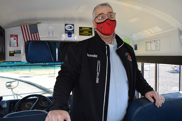 Driver Donald Kennedy teaches youngsters emergency procedures on a bus