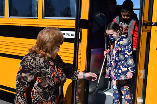 Instructional Assistant helps Marlee Bertram off the bus