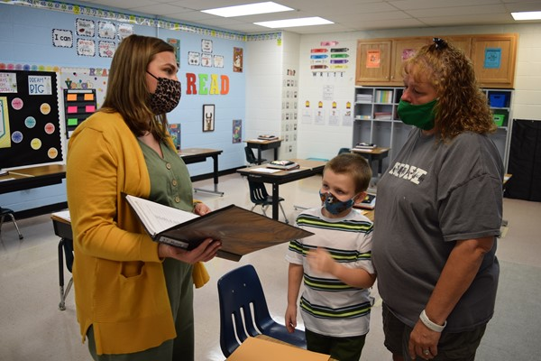 First Grade Teacher Caitlin Parmley shares information with Walker Adams and his mom