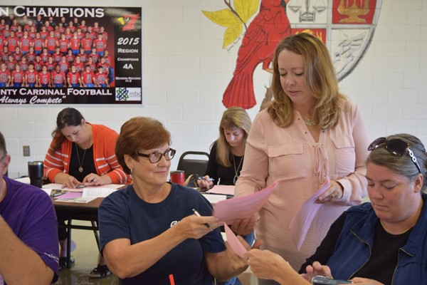 Kathryn Tucker hands out information to Monticello Elementary Cook Edith Ball and Monticello Elementary Manager Angel Polson