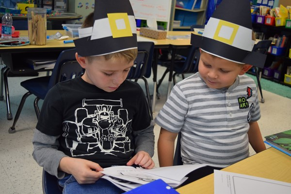 Boys studying with pilgrim hats on