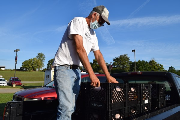 Driver unloads milk jugs from pickup truck bed to be sent to distribution sites