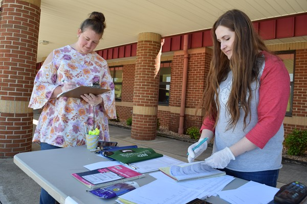 Instructional Asst Beth Craig and Yearbook Advisor Logan Anderson worked on paperwork distributing yearbook