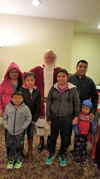 family poses with santa at the christmas party