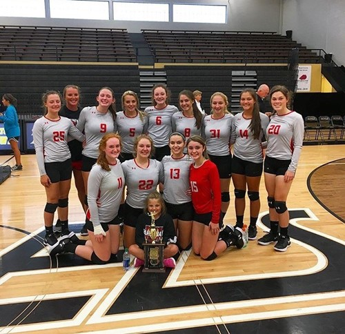 girls volleyball team with trophy