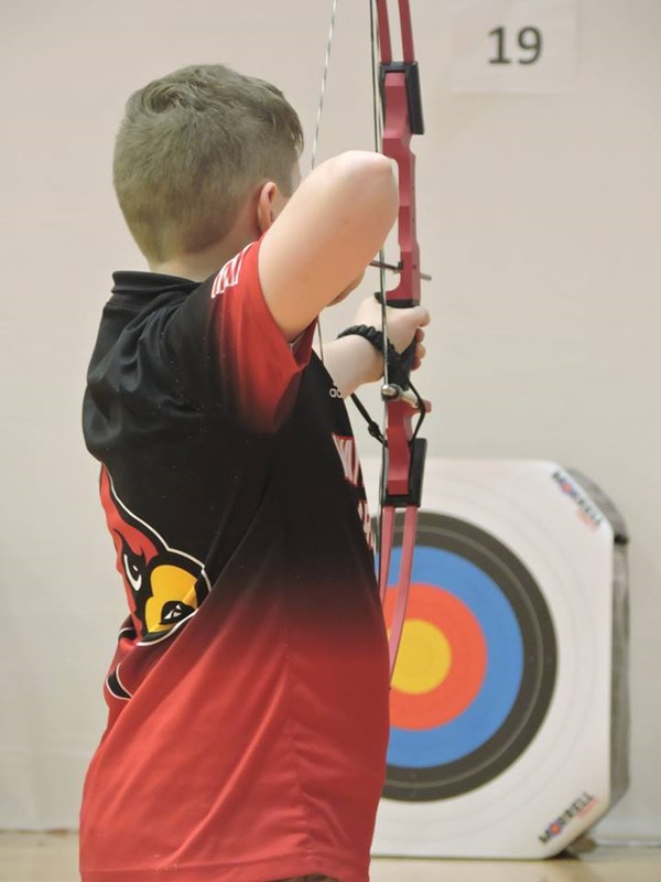 Nathanael Wright aiming at the target whilst pulling back his drawstrings