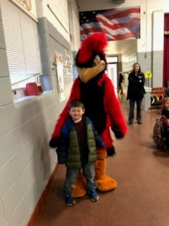 Cardinal posing with elementary student\