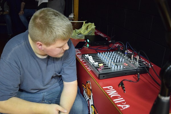 Lucas McGinnis managing the sound equipment backstage
