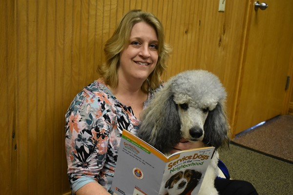 "Monticello Elementary Family Resource Center Director Leslie Randall and Winston reading """"Service Dogs in the Neighborhood"""