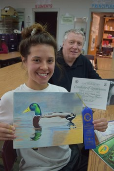 (L-R) Rylee Keith shows her work with her art instructor Tim Withers holding up her certificate