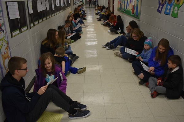 Wayne County students sitting in the kindergarden hallway working on literacy skills