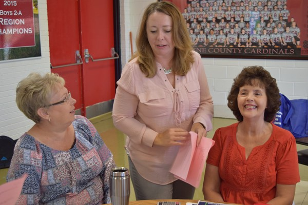Kathryn Tucker hands out information to WCMS Manager Debbie Swope and WCMS Cook Peggy McGinnis