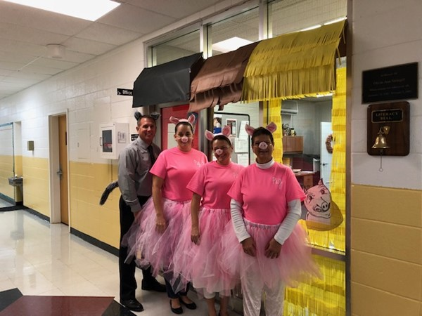 "(L-R) Prinicpal Derrick Harris, Cherish Jones, Rebecca Frost, and Dandy Riddle performed a skit of ""The Three Little Pigs"" to promote their Literacy Night"