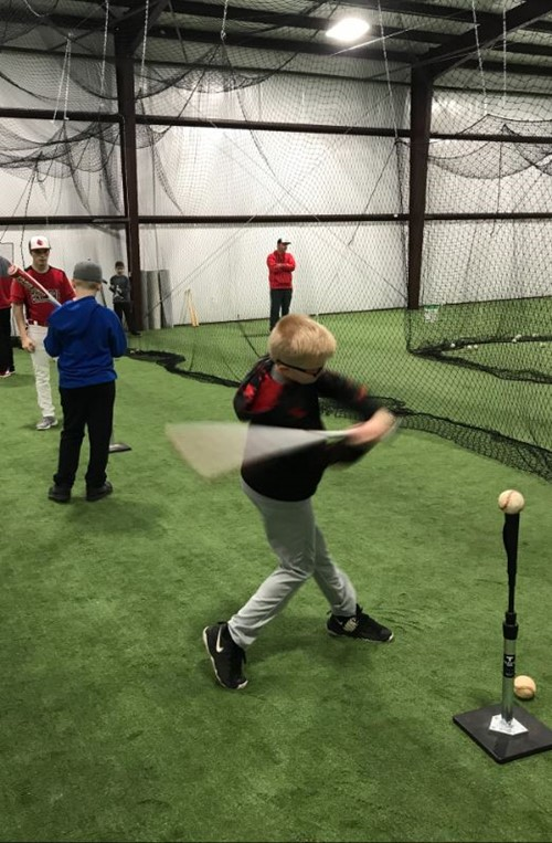 Young athletes practice their swings and hitting the ball