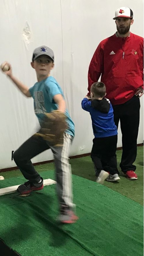 Coach Josh Bartley gives young student advice as he pitches the ball