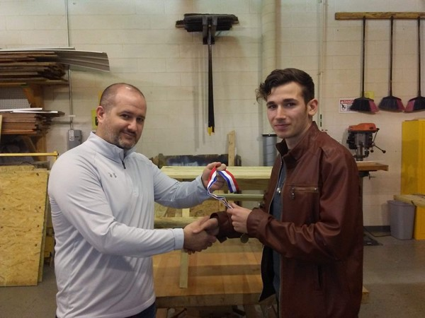 (L-R) Carpentry Teacher Josh Parmley presenting Ori Roysdon with a metal for placing 1st in Carpentry 1