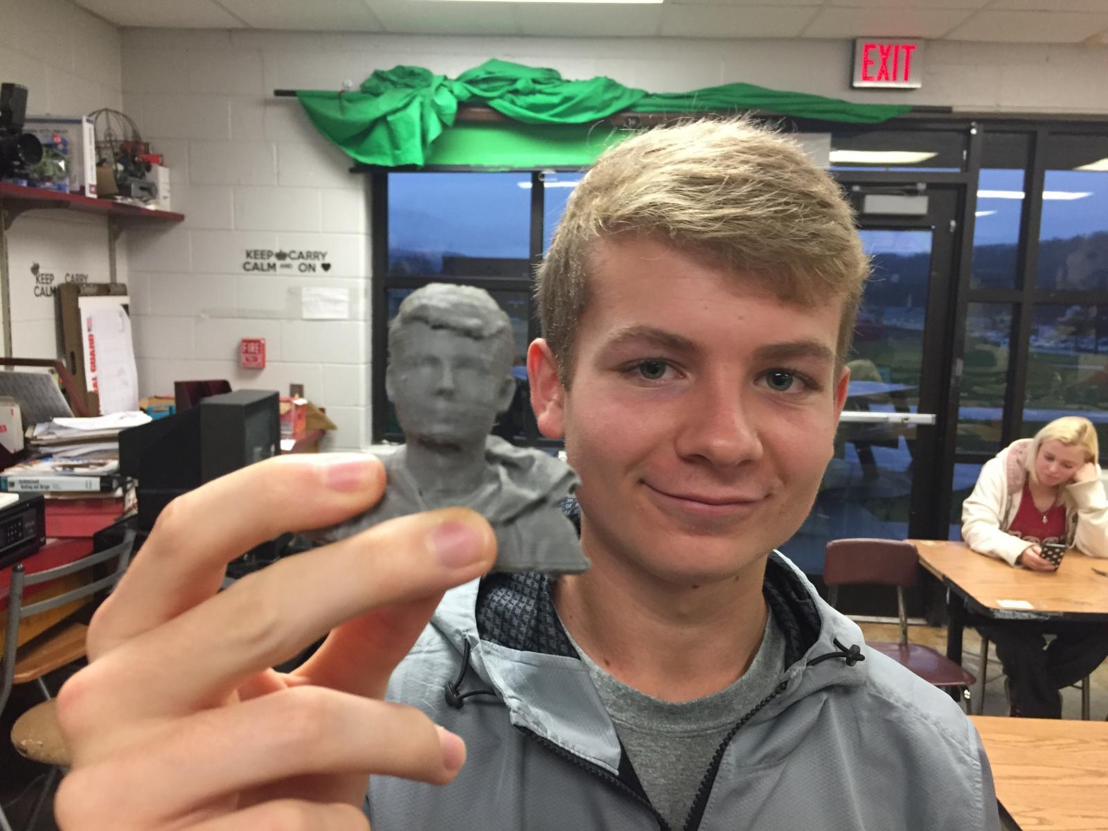 Ben Vickery holds a 3-D printed minature copy of himself