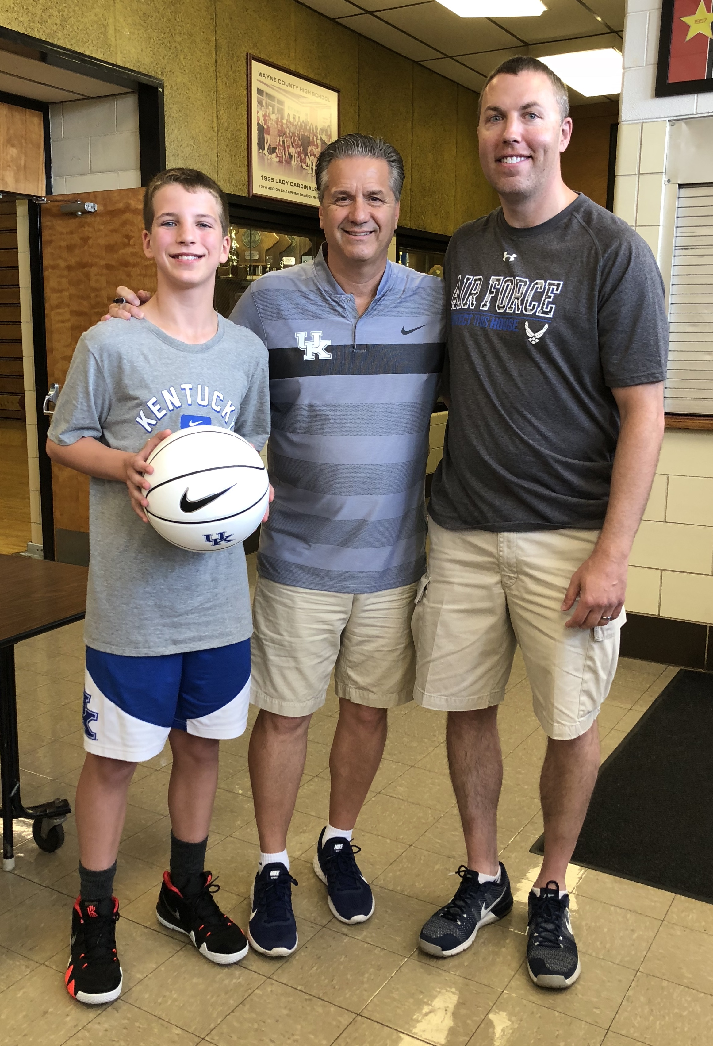 Kendall Phillips (left) and David Phillips (right) smiled with Coach John Calipari following the training clinic