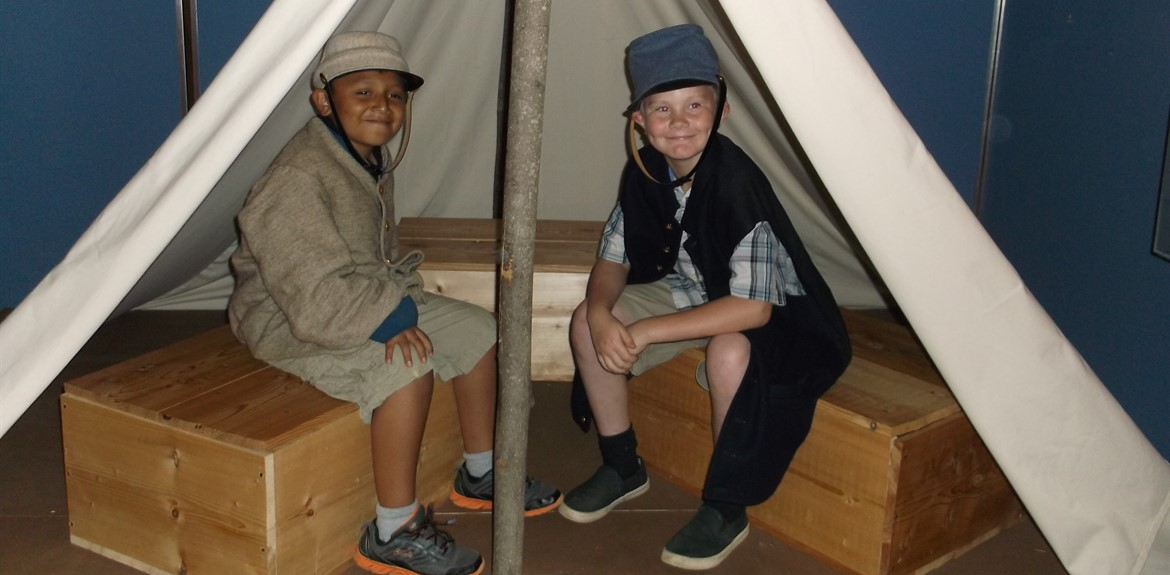 21st Century Students enjoy wearing replicas of Civil War uniforms and sitting beneath a tent at their very own campsite that coincided with a book they read at summer camp
