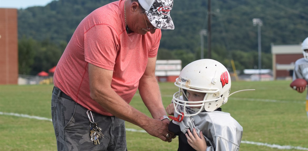 Youth League Football Coach Larry LaFevers assists a Grey Team youth football player adjust his shoulder pads