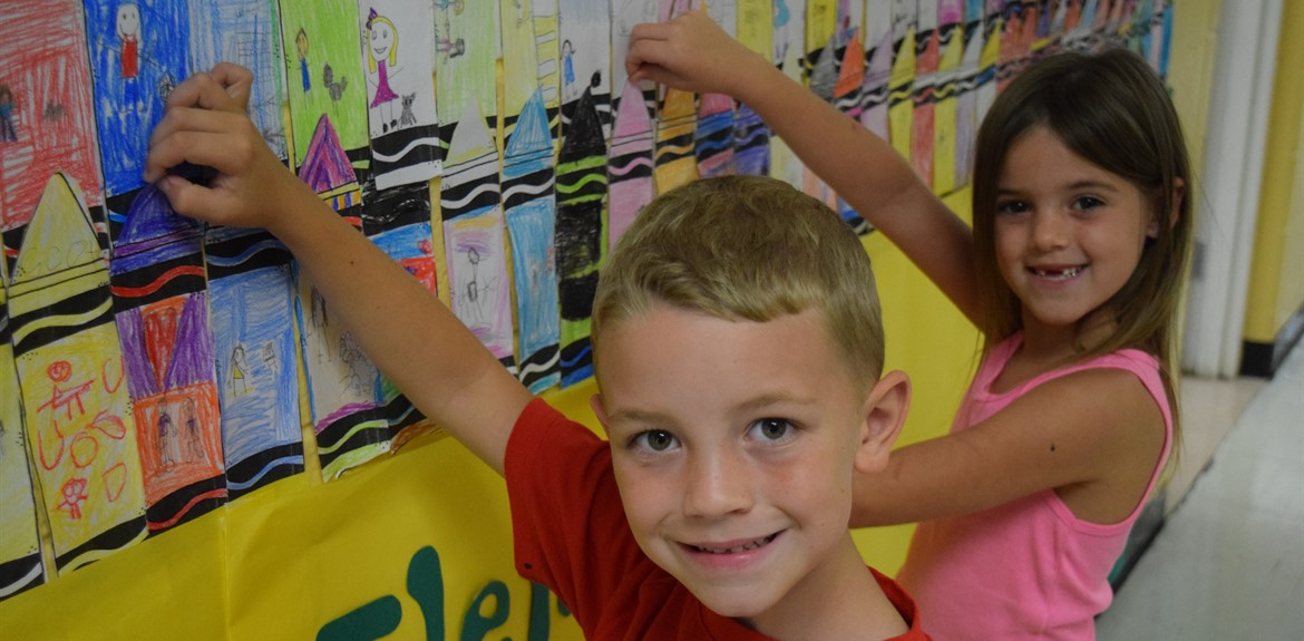 First Graders Dawson Leffew and Jazzlyn McGuire helped secure crayons on the wall for an art activity teaching diversity
