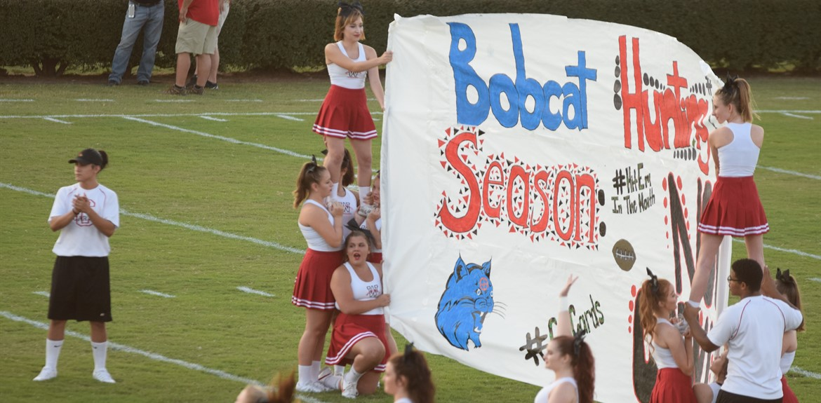 The WCHS cheer squad holds up the banner created by the pep club for the football team before their game against Bell County September 9