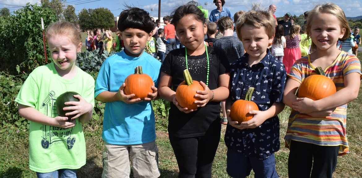 First graders enjoy pumpkins grown by the high school's agriculture classes