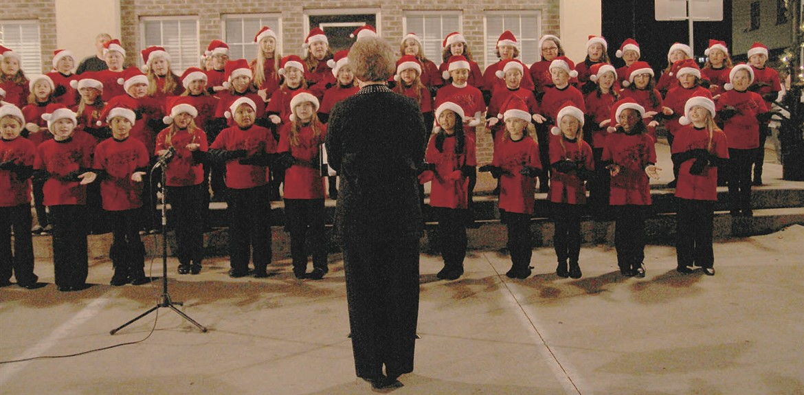 Anita Peters leads the Waynetonian Choir at the Annual Monticello Christmas Tree Lighting
