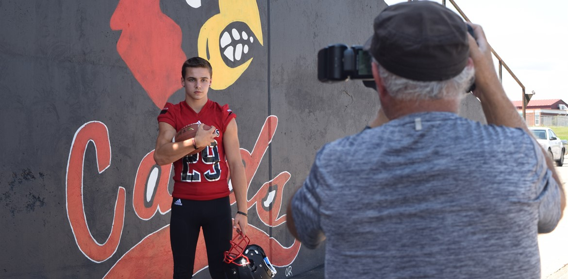 Noah Baker gets his individual football team photo taken by Sports Photographer Wade Upchurch