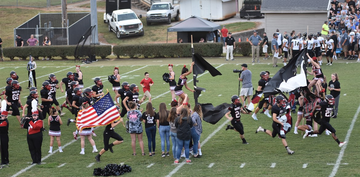 Wayne County Cards football team bursting through the banner at recent game